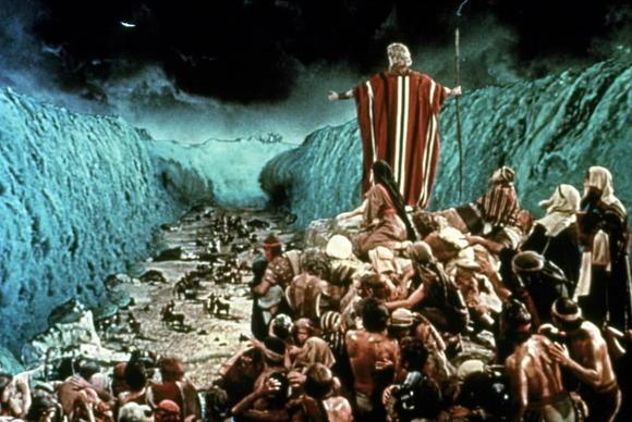 Moisés sostiene un bastón en su mano y frente a él el mar esta dividido en dos partes.