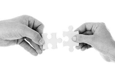 Dos piezas de un rompecabezas sostenidas por unas manos